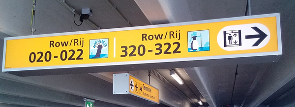 Figure 4. An example of a sign that supports multiple functions at once. This sign is an identification sign (you are at Row 020-022) and a directional sign (elevators are to the right). Photo by Donald Trung Quoc Don, 2019 (CC-BY-SA). bit.ly/3aqe12K.